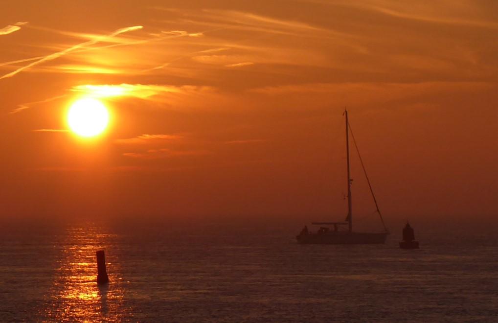 Orange-gelber Sonnenuntergang über dem Meer. Segelboot als Schatten erkennbar